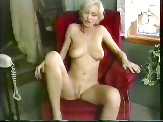 Blonde with awesome breasts fingers herself on the chair