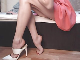 Amazing model shows her legs, feet, and white mules. Zoom.