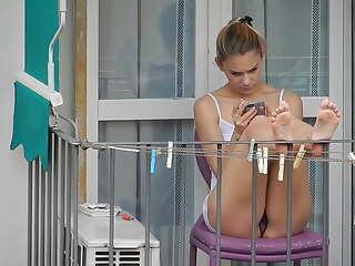 Teen neighbor shows upskirt on the balcony