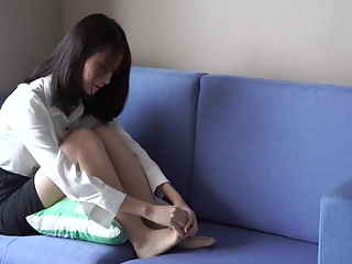 Girl massages her sore feet in tan nylon