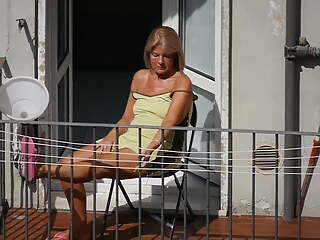 Tanned granny sunbathing on the balcony