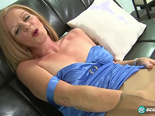 When this scene opens, Misty, a 51-year-old divorcee and accountant from Southern California, is wearing a short, tight blue dress. She sits down on a couch and spreads her legs, and we can see that she's wearing sheer pantyhose. She reaches down into her pantyhose and plays with her pussy.