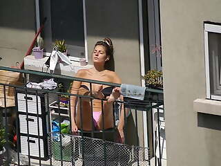 Unaware girl gets some sun on the balcony