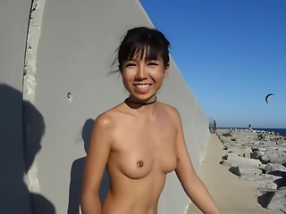 Skinny babe is doing some very naughty stuff on the beach, in the middle of the day